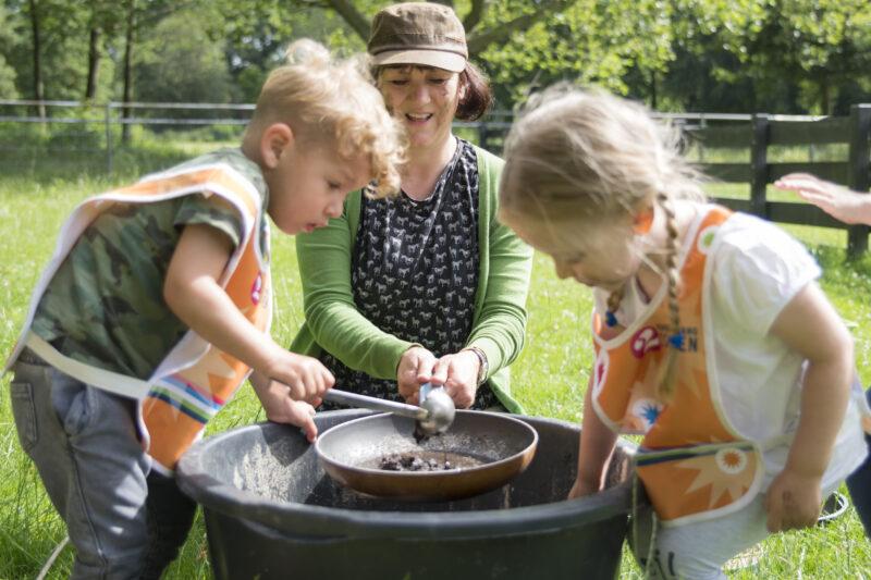 Kinderen spelen in de modderkeuken tijdens modderdag